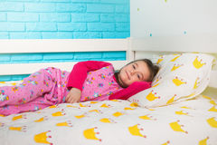 Little girl in pajamas lying in bed in the morning. Pretty little girl in pajamas lying in bed in the morning Royalty Free Stock Photo
