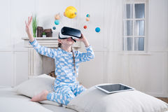 Little girl in pajamas playing in virtual reality headset Stock Image