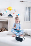 Little girl in pajamas sitting on bed and using digital tablet Royalty Free Stock Image