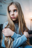 Little girl in pajamas sitting with crossed arms and looking away Royalty Free Stock Photos
