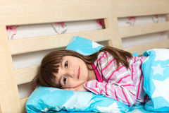 Little girl in pajamas sleep in bed under a blue blanket. Beautiful little girl in pajamas sleep in bed under a blue blanket Stock Photo
