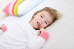 Little girl in pajamas on sunny morning Stock Photos