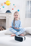 Little girl in pajamas using digital tablet on bed Stock Photo