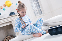 Little girl in pajamas using digital tablet Royalty Free Stock Photography