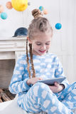 Little girl in pajamas using digital tablet Stock Photo