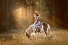 Little girl with palomino miniature horse in summer day