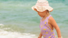 Little Girl in Panama Goes out of Sea Water to Beach. Closeup little blond girl in swimsuit and panama goes out of azure sea water across foamy wave to sand stock footage