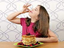 Little girl with pancakes and ok hand sign Royalty Free Stock Images
