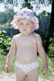Little girl in a pants standing on the beach near the bushes. Stock Photo