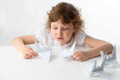 Little girl with paper cranes Stock Image