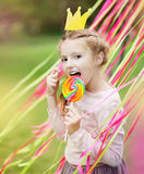Little girl with a paper crown and a bright lollipop Stock Photo