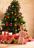 Little girl with parcels round Christmas tree. Excited Stock Image