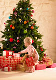 Little girl with parcels round Christmas tree. Holding teddy bear Royalty Free Stock Images