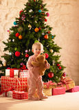Little girl with parcels round Christmas tree. Holding teddy bear Stock Photo