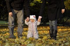 Little girl with parents. Parents in autumn park are holding baby and helping make first steps Royalty Free Stock Photography