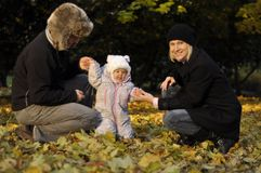 Little girl with parents. Parents in autumn park are holding baby and helping make first steps Stock Photo