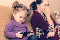 A little girl without parents` attention looks at the smartphone stock photo