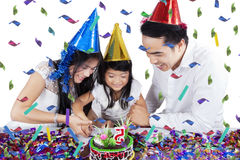 Little girl and parents cut birthday cake Stock Photos