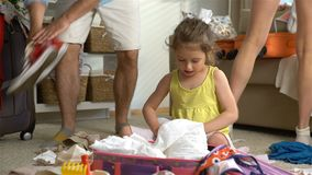 Little Girl with Parents Packing a Luggage for a Journey. Happy little girl with her parents is carefully packing a luggage for a new journey stock video footage