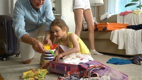 Little girl with parents packing a luggage for a journey. Happy little girl with her parents is carefully packing a luggage for a new journey. Slow Motion stock footage