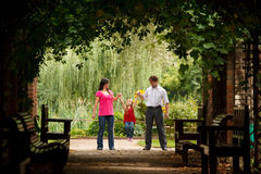 Little girl with parents in park in plant tunnel Stock Photography