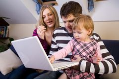 Little girl with parents play with a laptop