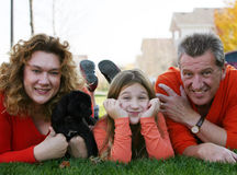 Little girl with parents and puppy outside Royalty Free Stock Photo