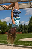 Little Girl in the Park. Little blond girl hanging upside down on play structure in the park Stock Photography