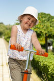 Little girl in the park. Little adorable girl posing with orange scooter in the park Royalty Free Stock Photos
