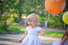 LIttle girl in the park with baloons Royalty Free Stock Photo