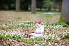 Little girl in the park among beautiful spring flowers Royalty Free Stock Images