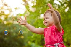 Little girl at park with bubbles Stock Image