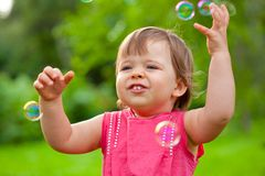 Little girl at park with bubbles Royalty Free Stock Photo