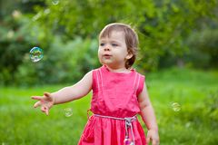 Little girl at park with bubbles Stock Images