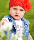 Little girl in the park closeup on a background of green grass. In summer Royalty Free Stock Photo