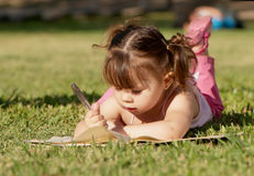 The little girl in  park, drawing in a writing Royalty Free Stock Photography