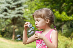 Little girl in the park inflates soap bubbles Stock Images