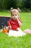 Little girl in the park. learn to read. Royalty Free Stock Photography