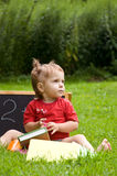 Little girl in the park. learn to read. Stock Photo