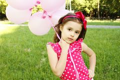 Little Girl in the Park with pink balloons Stock Photo