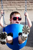 Little Girl at Park on swing. With sunglasses Stock Images