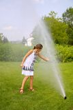 Little girl in park under water splashes Stock Images