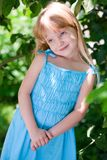 Little girl in the park wearing blue dress Royalty Free Stock Photos