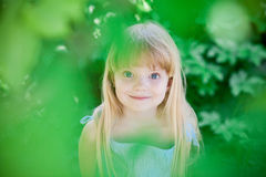 Little girl in park wearing blue dress Stock Photo