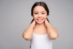 Little girl with patches on elbows stock photo