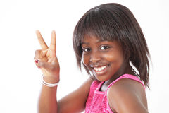 Little girl peace sign. Smiling little girl making peace sign with fingers royalty free stock photo