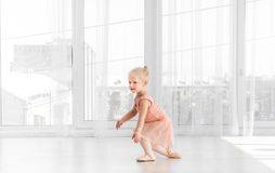Little girl in peachy dress and pointe shoes dancing in the room Stock Photos