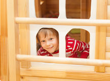 Little girl peaks out the window Royalty Free Stock Photo
