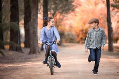 girl on a bicycle and boy running beside on the path of a park stock photos