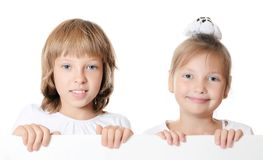 Little girl peeking from behind the advert Stock Image